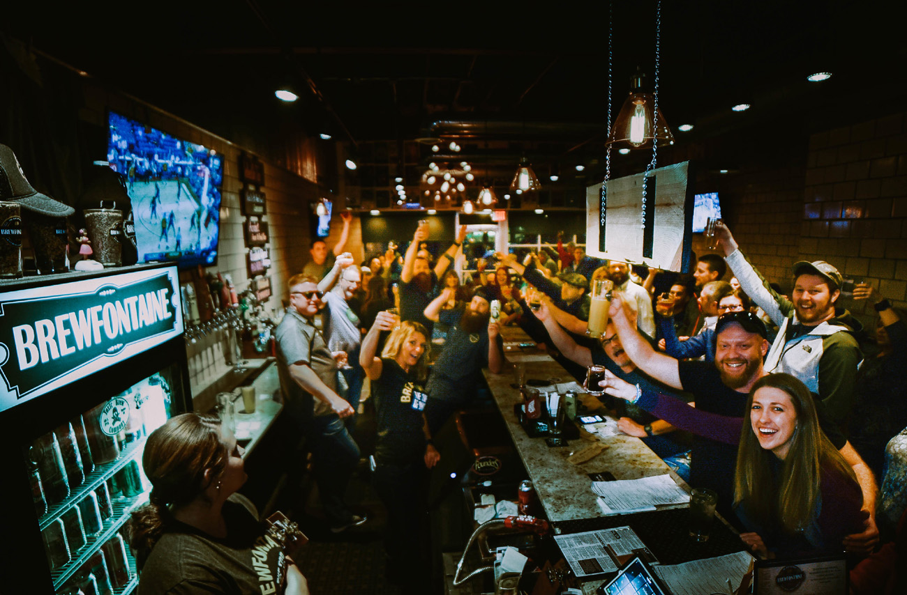 Brewfontaine staff and customers raise their glasses in a toast.
